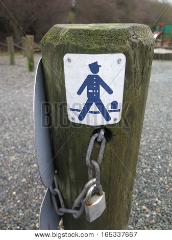 Notice on post depicting a blue Gendarm policeman guarding coastal path along Flensburg Fjord in Denmark