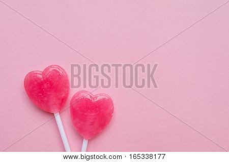 two Pink Valentine's day heart shape lollipop candies on empty pastel pink paper background. Love Concept. Knolling top view. Minimalism colorful hipster style.