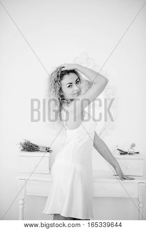 Curly Blonde Girl In A White Silk Gown Boudoir Robe Background Mirror. Black And White Photo