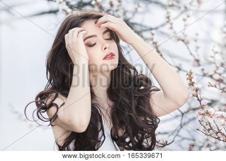 Sensual young girl standing in white dress at blossoming tree in the garden against white background. Beauty of woman and nature consept. Portrait of beautiful model with curly brown hair sensual posing with closed eyes.
