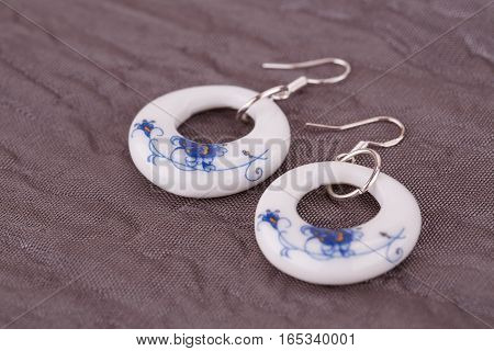 Ceramic earrings on fabric background, close up picture.