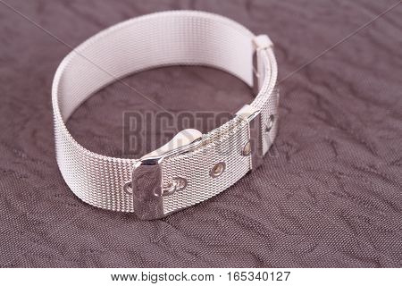 Silver bracelet on fabric background, close up picture.