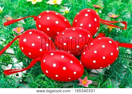 Easter red spotted eggs on artificial grass background.