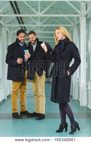 Blond businesswoman holding smart phone in lobby with colleagues at background.