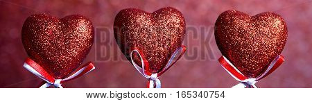 Valentines day. Red hearts on red blurred background closeup with copy space for congratulation, border design panoramic banner