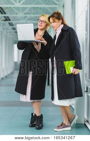 Two elegant businesswomen working together on a project at lobby.