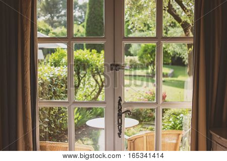 Nature behind the door. White frames with glass panels. Mansion with a garden.