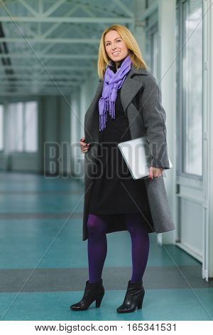 Portrait of smiling blond businesswoman holding laptop.
