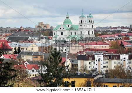 Panoramic view of Grodno, Belarus. The historic city center with red tile roofs and the old Catholic church in the Baroque style during the day.
