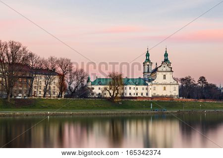 Church On The Skalka In Old Town In Krakow With Reflection In The River, Poland. Long Time Exposure