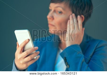 Businesswoman making selfie photo portrait with mobile smart phone in office
