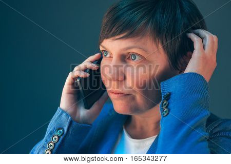 Nervous worried businesswoman during unpleasant telephone conversation with mobile phone