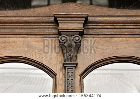 Decorative element of old wooden window with carved decorative element with flourishes.