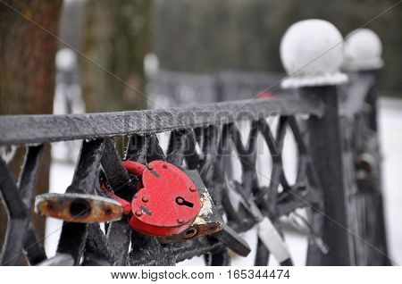 Black metal fence with a hanging red closed padlock in the shape of heart close up.