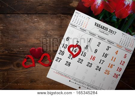 A calendar with hearts on the wooden table