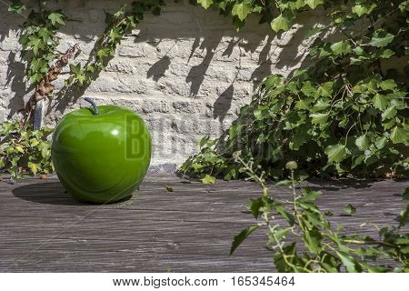 Big green artificial apple on the wooden stand with green leaves