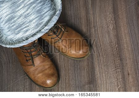 Two brown boots with grey hat on the wooden background