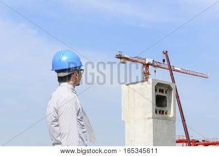The construction engineer looking at the construction site and crain