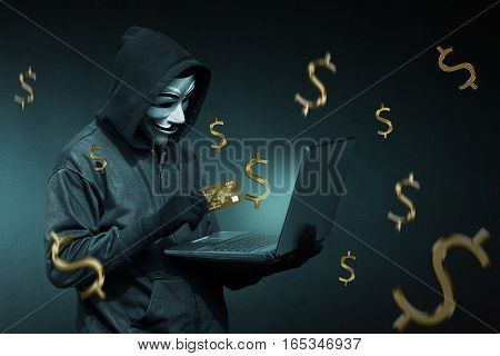 Hooded Hacker With Credit Card Stealing Data From A Laptop
