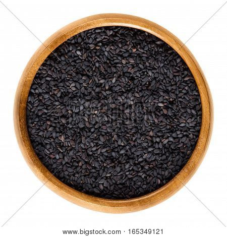 Black sesame seeds in wooden bowl. Fruits of Sesamum radiatum, also black benniseed or vegetable sesame, is eaten whole or as paste. Isolated macro food photo close up from above on white background.