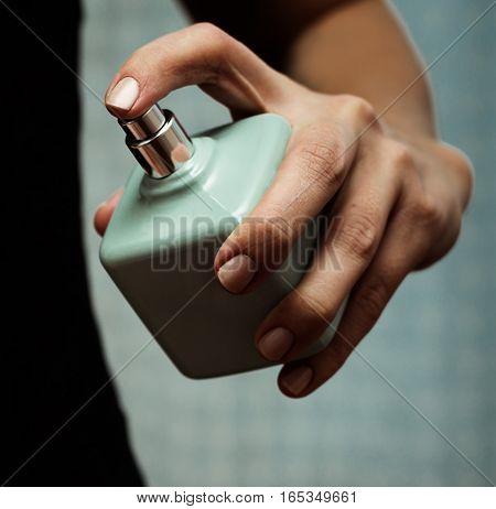 closeup Perfume blue bottle in female hand