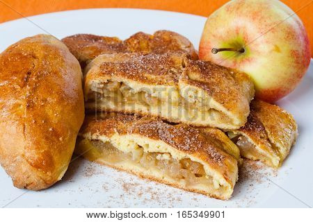 Apple pie and cake slices on white plate. Apple fruit with home made baked dessert. orange background