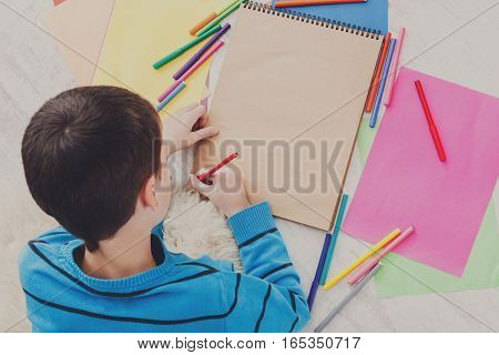 Boy drawing picture with colored markers, crayons and pencils. Top view from above, copy space on paper sheet. Creative children, child art school or courses concept