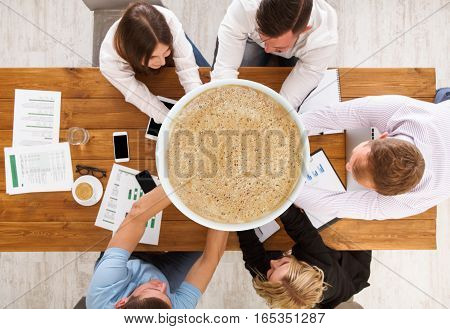 Team put hands together holding giantic cup of coffee, top view of working table. Collage of teambuilding in office, young businessmen and women in casual unite hands