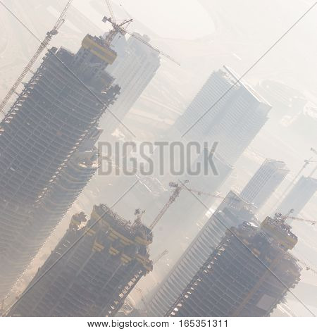 Huge skyscrappers construction site with cranes on top of buildings. Rapid urban and construction sector development or inflation of real estate bubble.