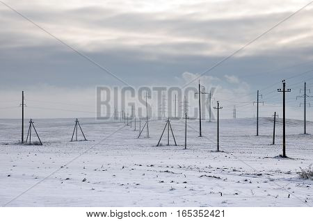 Snowy winter field with many power lines.