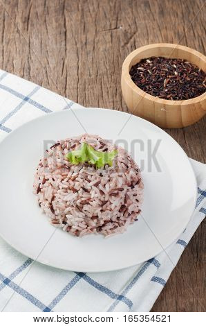 kitchen table with rice berry and rice grain on wood plate. thai local food selective focus on top view.