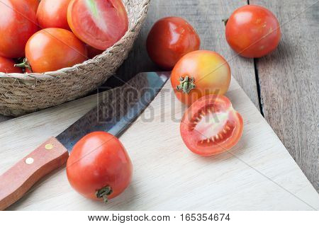 kitchen table with slice fresh tomatoes on wood basket selective focus on top view.
