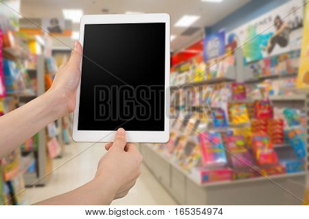 human hand hold blank screen smart phone tablet cellphone on blurry bookshelf in bookstore authentication permission shopping online concept.