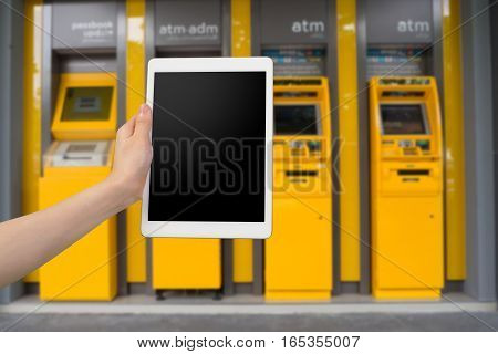 human hand hold smartphone tablet cell phone with blank screen on blurry cash machines background authentication permission user concept.
