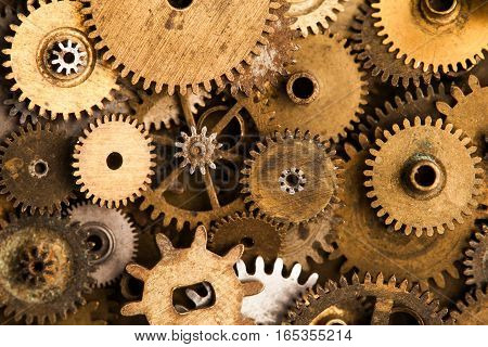 Aged gears cogwheels background. Retro mechanical clock accessories close-up. Shallow depth field, soft focus.