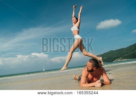 young couple fooling around on the beach. The guy and the girl model looks tanned and happy life on a tropical beach.