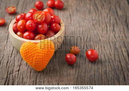 kitchen table with dwarf tomatoes on wood plate with orange heart shape. healthy eating and dieting food concept of health care Image focus top view.