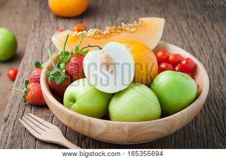 variety fresh fruits on wood plate and forkstrawberrymelontomatoes. mix variety high fructose fruits on kitchen table. healthy eating and dieting food concept of health care Image focus top view.