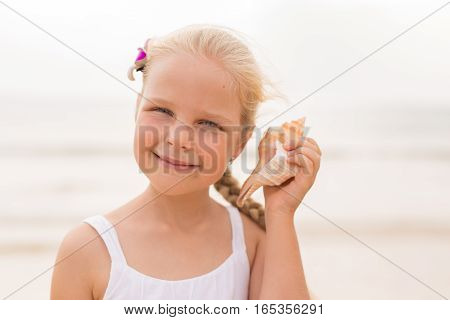 Little girl by the sea listening to seashell