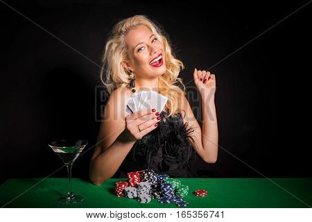 Lucky woman playing poker and celebrating her win