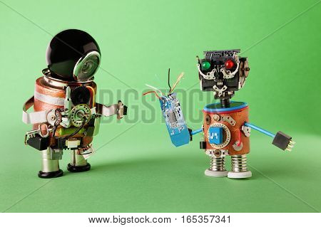 Funny toy robots with tech accessories. Handyman with screwdriver and technician worker character handing circuit micro chip. Modern steampunk heroes concept. green background.