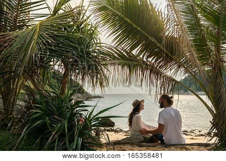 The guy and the girl model looks happy life on a tropical beach at sunset. Together.