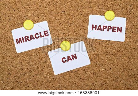 Text Miracle Can Happen on white stickers pinned on cork board