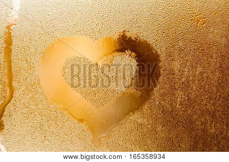 Love heart shape and raindrops textured pattern. Abstract golden color window with water droplet, liquid bubbles. macro view. Shallow depth of field. Valentines day concept.