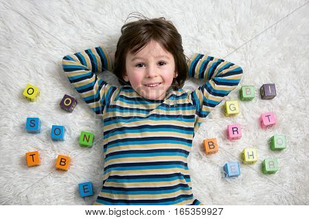 Cute Child, Boy, Play With Toy Blocks, Lying On The Floor