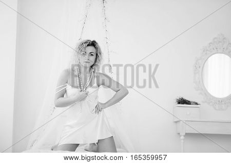 Curly Blonde Girl In A White Silk Gown Boudoir Robe On Bed. Black And White Photo