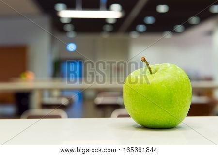 Interior of cafeteria with fresh green apple on table