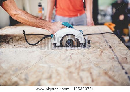 Construction Worker Using Slider Compound Mitre Saw Or Circular Saw For Cutting Massive Wood Board.