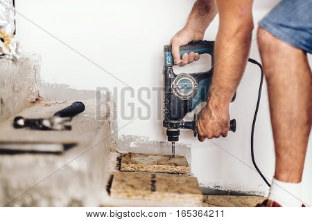 Industrial Construction Worker Drilling Holes In Wooden Board And Concrete Using Professional Machin