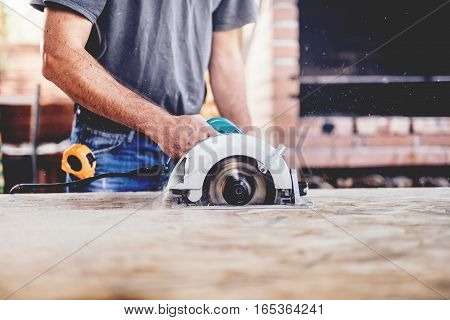 Construction Worker, Industrial Carpenter Using Circular Miter Saw For Cutting Boards